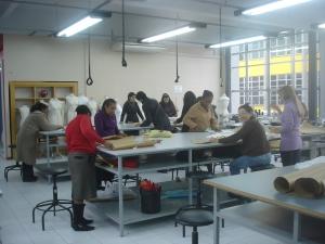 As mulheres cortando o tecido